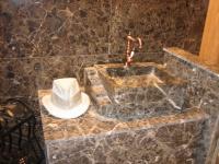 Agencement de salle de bains en marbre marron Emperador. Fabrication de vasque massive sur mesure. Vente de robinetterie en laiton.