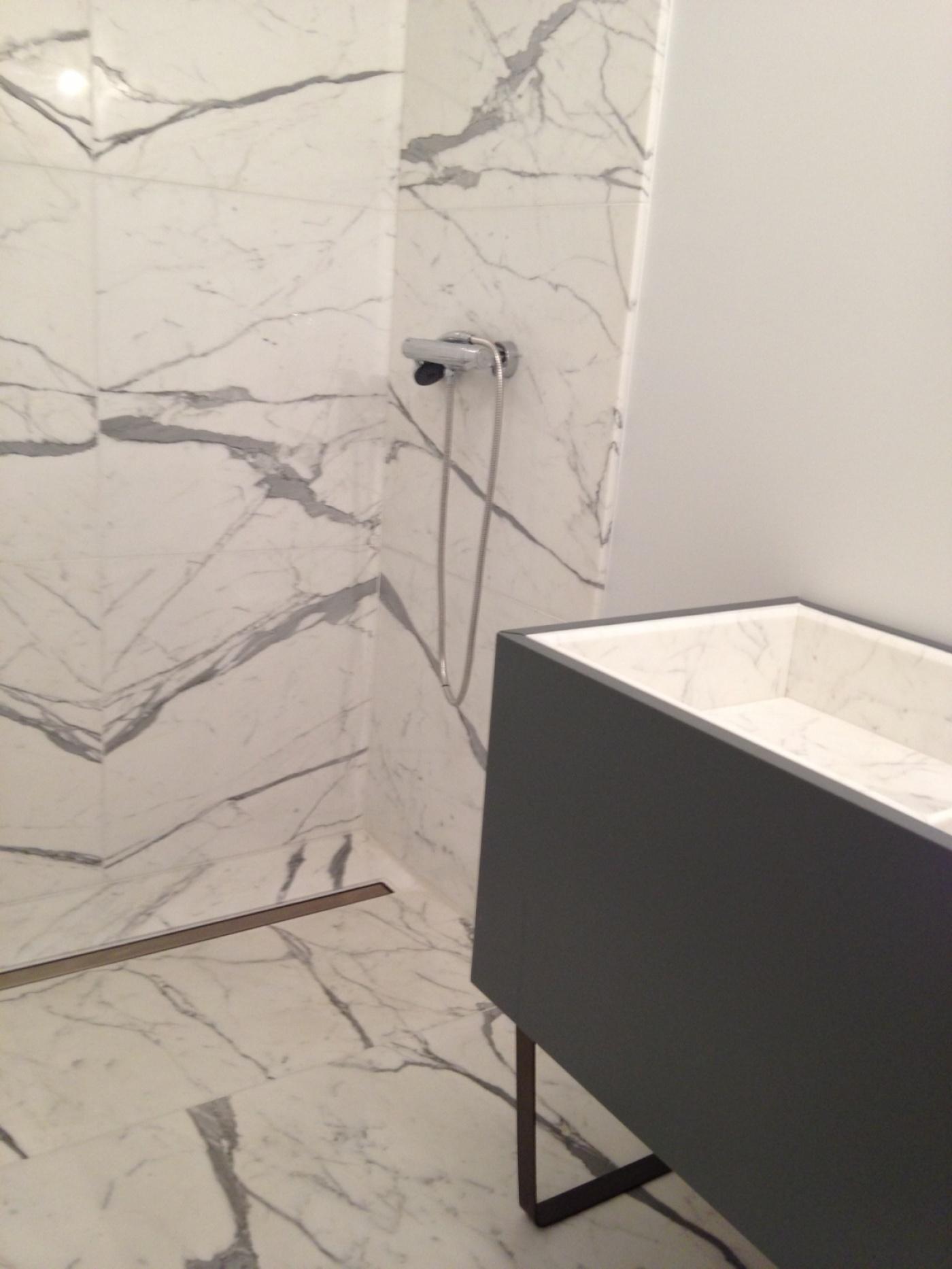 Salle de bains avec murs, bac à douche, et vasque Bianco Statuario Extra sur meuble Altamarea Must (design Willy Dalto). Chantier à Montgenevre